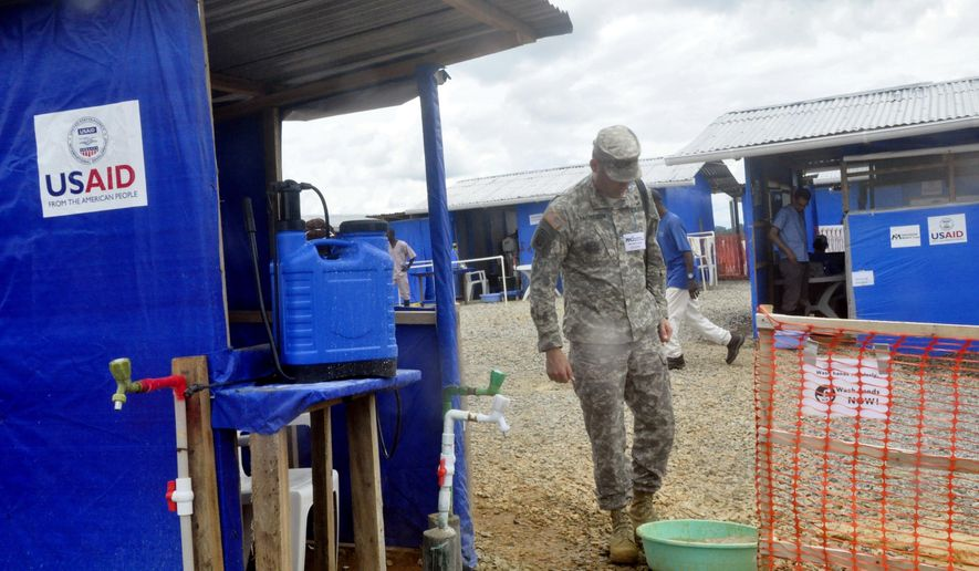 A member of the U.S army walks past a newly constructed Ebola treatment centre in Bongcounty, on the outskirts of Monrovia, Liberia, Tuesday Oct. 7, 2014. Liberia has been among the hardest hit nations at the center of the long outbreak, which has killed more than 3,000 people. As of Friday, there had been 3,834 confirmed Ebola cases and 2,069 deaths in Liberia, according to the World Health Organization. Forty-four percent of those cases were reported in the past three weeks, a signal that the infectious disease is spreading. (AP Photo/Abbas Duller)