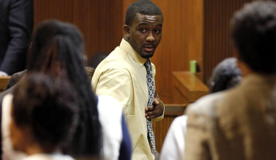 Desmonte Leonard points to family members as he leave the courtroom after a jury found him guilty of capital murder, Tuesday, Oct. 7, 2014, in Opelika, Ala., in the killing two former Auburn University football players and a third man. (AP Photo/Opelika-Auburn News, Todd J. Van Emst)