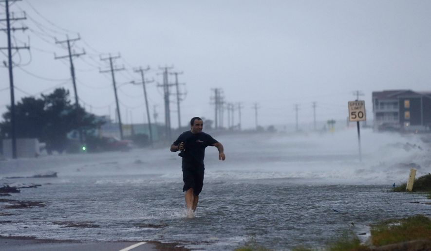 FILE - In this July 4, 2014 file photo, a man crosses a flooded Highway 64 as wind pushes water over the road as Hurricane Arthur passes through Nags Head, N.C. This year's Atlantic hurricane season has so far had the fewest number of storms since 1983, with only five named storms forming so far in the region: Arthur, Bertha, Cristobal, Dolly and Edouard. (AP Photo/Gerry Broome, File) **FILE**