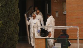 A fireman gestures, bottom right, as workers wearing rompers and gloves come out of the entrance of the apartment building of a Spanish nurse infected with Ebola in Madrid, Spain, Wednesday, Oct. 8, 2014. Three more people were placed under quarantine for Ebola at a Madrid hospital where the Spanish nurse became infected, authorities said Thursday. More than 50 other possible contacts were being monitored. The nurse, who had cared for a Spanish priest who died of Ebola, was the first case of Ebola being transmitted outside of West Africa, where a months-long outbreak has killed at least 3,500 people and infected at least twice as many. (AP Photo/Andres Kudacki)
