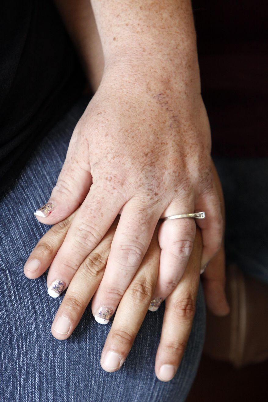 Aimee McCarter and Jen Kozushko hold hands as they wait for the Clerk of the District Court office to open for the afternoon to apply for a marriage license on Tuesday, Oct. 7, 2014, at the Reno County Courthouse in Hutchinson, Kan. The couple was informed later in the day of the application's denial. (AP Photo/The Hutchinson News, Lindsey Bauman)