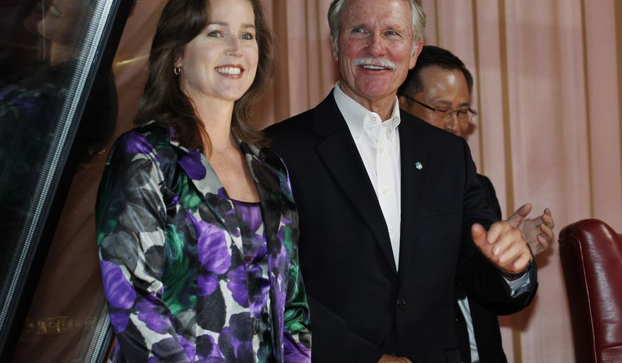 FILE - In this Sept. 13, 2011 file photo, Oregon Gov. John Kitzhaber, right, and his companion, Cylvia Hayes, react to a welcome from attendees at the awarding ceremony of the Enjoy Oregon Wine Fair in Tokyo. On Wednesday, Oct. 8, 2014, Portland's alternative weekly newspaper, the Willamette Week, reported that Kitzhaber's fiancee, Hayes, has used her role as an adviser to Kitzhaber to land contracts for her long-time job as a consultant on energy matters. (AP Photo/Hiro Komae, file)