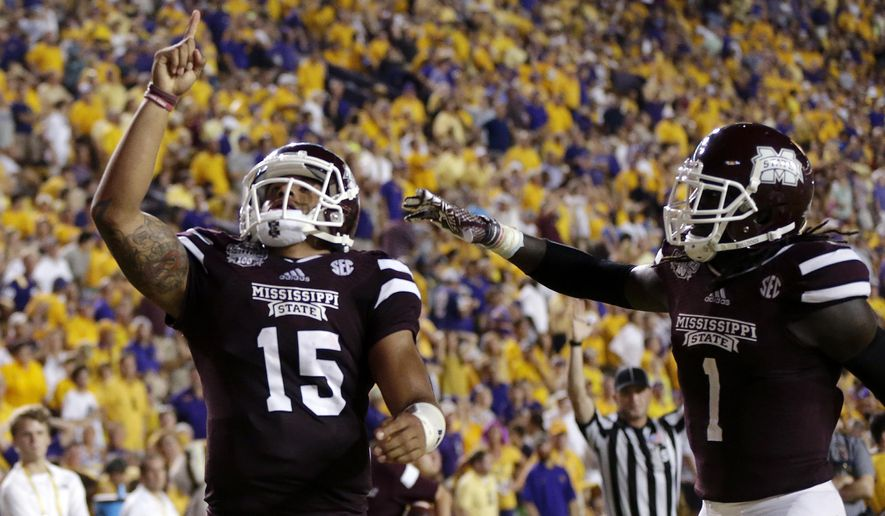 FILE - In this Sept. 20, 2014, file photo, Mississippi State quarterback Dak Prescott (15) celebrates his 56-yard touchdown run with wide receiver De'Runnya Wilson (1) in the second half of an NCAA college football game against LSU in Baton Rouge, La. No. 3 Mississippi State, No. 9 TCU, No. 10 Arizona and No. 22 Georgia Tech are all unbeaten after starting the season unranked. (AP Photo/Gerald Herbert, File)