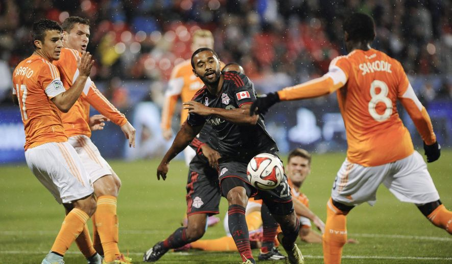 Toronto FC's Luke Moore, center, attempts to get the ball past Houston Dynamo's Bryan Salazar during first-half MLS soccer game action in Toronto, Wednesday, Oct. 8, 2014. (AP Photo/The Canadian Press, Hannah Yoon)