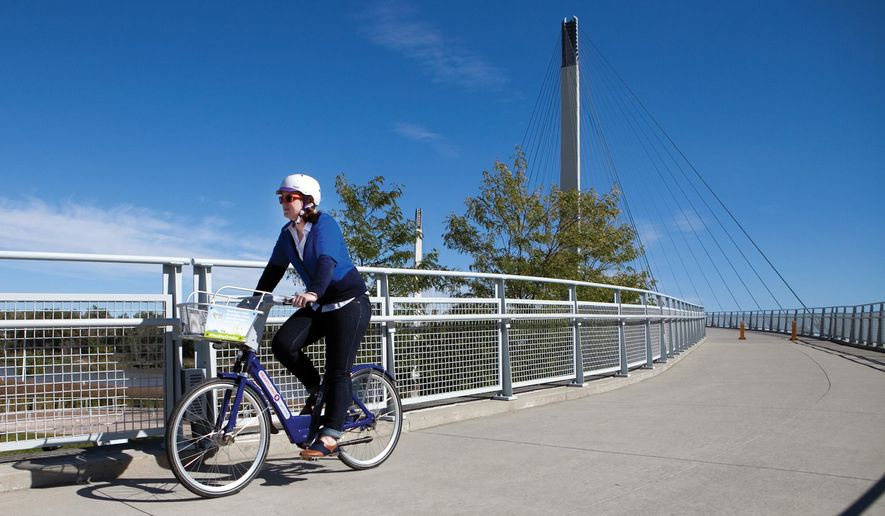 A woman rides a bike rented from Heartland B-cycle toward Omaha on the Bob Kerrey Pedestrian Bridge on Tuesday, Oct. 7, 2014 between Council Bluffs, Iowa and Omaha, Neb. Heartland B-cycle is a public program in which riders can check out bikes from several stations positioned across Omaha and Council Bluffs by purchasing daily, monthly or annual passes. (AP Photo/The Daily Nonpareil, Joe Shearer)