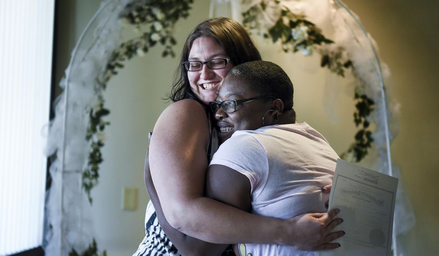 Jana Hayes, left, and Angie Hayes embrace under an altar at the Citizens Service Center in Colorado Springs, Colo., Tuesday, Oct. 7, 2014, after self-officiating their own marriage and becoming the first same-sex couple to legally wed in El Paso County. Colorado Attorney General John Suthers ordered clerks in all of the state's 64 counties to issue marriage licenses to gay couples after the Colorado Supreme Court lifted previous orders barring clerks in Denver and Boulder from doing so. (AP Photo/The Colorado Springs Gazette, Michael Ciaglo)