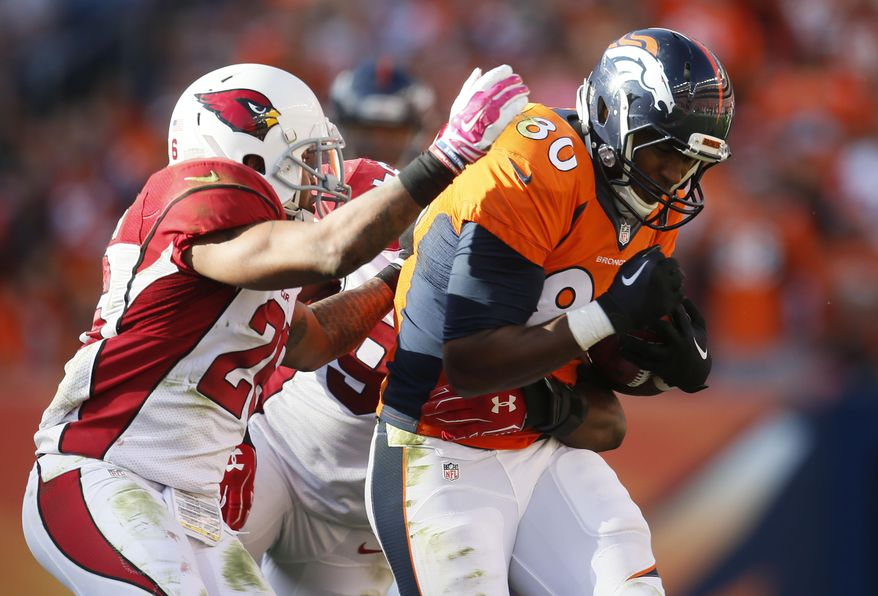 Denver Broncos tight end Julius Thomas (80) is tackled by Arizona Cardinals free safety Rashad Johnson during the second half of an NFL football game, Sunday, Oct. 5, 2014, in Denver. (AP Photo/Joe Mahoney)