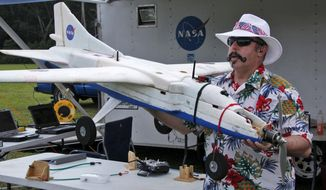 In this Friday Sept. 19. 2014 photo provided by NASA Langley Research Center, Mike Logan, a UAV engineer at NASA Langley, carries a UAV drone to the grassy airstrip of the Aviation History Museum in Pungo, Va. NASA is partnering with the U.S. Fish and Wildlife Service to test the use of drones to spot wildfires in the Great Dismal Swamp in southeastern Virginia and northeast North Carolina. (AP Photo/NASA Langley Research Center, David C. Bowman)