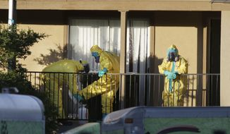 FILE - In this Oct. 5, 2014 file photo, hazardous material cleaners disinfectant their personal protective equipment after working in the apartment where Thomas Eric Duncan, the Ebola patient who traveled from Liberia to Dallas, stayed last week, in Dallas.  The Homeland Security Department has ordered agents at airports and other ports of entry to observe everyone coming into the United States for potential signs of Ebola infection, officials said Wednesday. Homeland Security Deputy Secretary Alejandro Mayorkas said Customs and Border Protection agents are also handing out factsheets to travelers with details of what symptoms to look for and directions to call a doctor if they become sick within 21 days. (AP Photo/LM Otero, File)