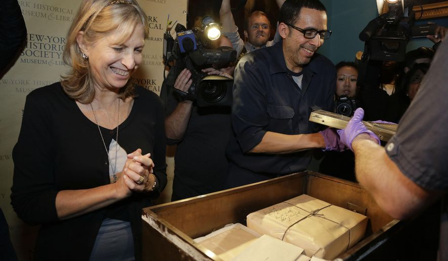 New-York Historical Society curator of decorative arts Margaret Hofer, left, reacts upon seeing some of the contents of a time capsule from 1914 as art handler Daniel Santiago, right, lifts off the lid during a ceremony, Wednesday, Oct. 8, 2014, in New York. The capsule, stored by the Lower Wall Street Business Men's Association, was to have been opened in 1974 but was forgotten. Inside were documents depicting life in 1914, from the tea, coffee and spice business to baseball and bullfights. (AP Photo/Julie Jacobson)