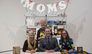 """This September 2014 photo provided by Crystal Bridges Museum of American Art shows artist Andy Ducett with his mom Marilyn behind him and two volunteers at the Mom Booth at the museum in Bentonville, Ark. The Mom Booth is the opening exhibit in a new show of contemporary art at Crystal Bridges called """"State of the Art."""" Ducett sees the piece as a way to challenge visitors' ideas about what art is by taking something familiar _ the concept of mom _ out of context and putting it in a museum setting. The booth is staffed by a rotating group of local volunteers. (AP Photo/Marc Henning)"""
