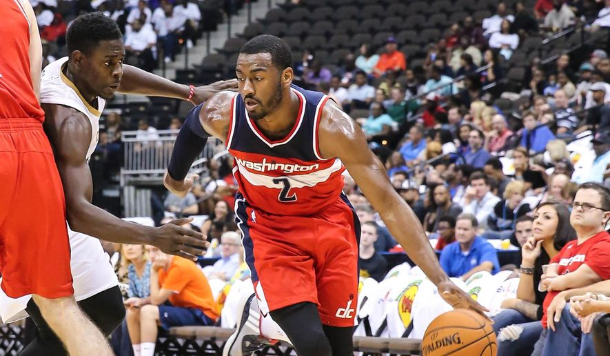Washington Wizards' John Wall (2) drives for the basket while defended by New Orleans Pelicans' Jrue Holiday during the first half of an NBA preseason basketball game in Jacksonville, Fla., Wednesday, Oct. 8, 2014. (AP Photo/Gary McCullough)
