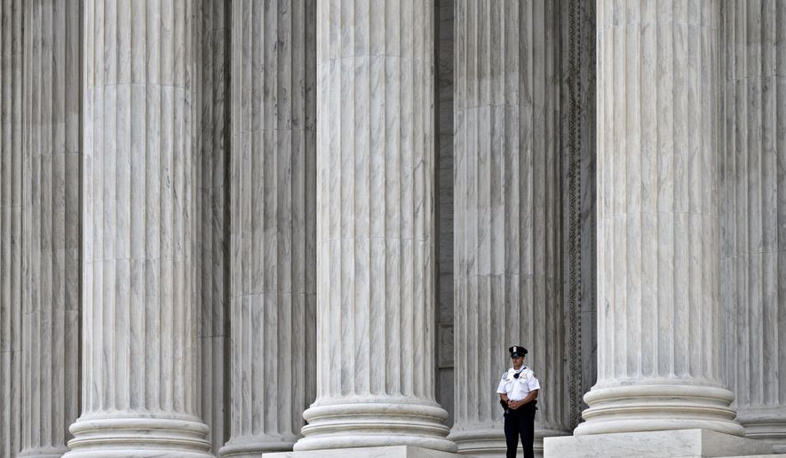 In this Oct. 7, 2014, photo, a police officer is dwarfed amid the marble columns of the Supreme Court in Washington. Some warehouse workers who fill orders for Amazon.com customers say they spend up to 25 minutes after every shift waiting to pass through security checks to make sure they aren't stealing from the online retailer. But they don't get paid for the extra time. The Supreme Court hears arguments Wednesday in a lawsuit filed by two former staffers at a Nevada warehouse who claim they should be compensated for time spent in security screenings under the Fair Labor Standards Act.  (AP Photo/J. Scott Applewhite)