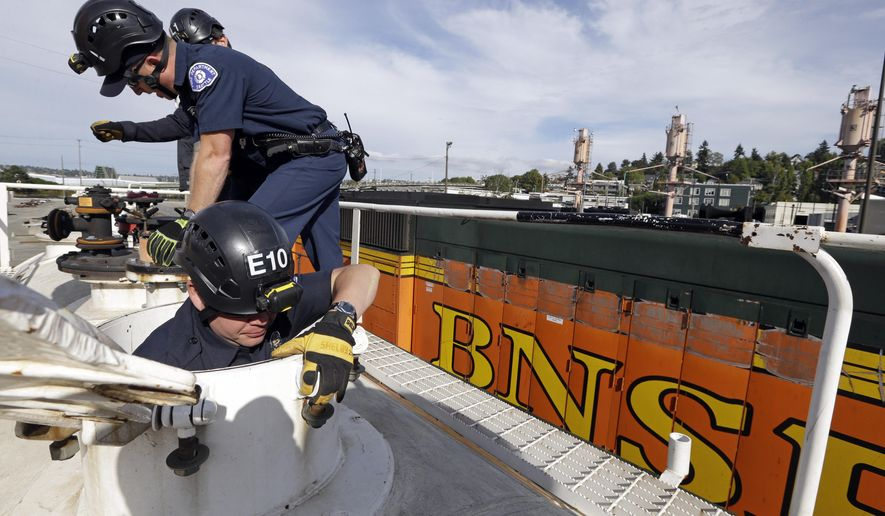 A Seattle firefighter climbs inside a training tank car as others examine valves during a specialized training session on how to respond to incidents involving oil trains, Wednesday, Oct. 8, 2014, in Seattle. BNSF is training several dozen firefighters from Seattle and neighboring cities on how to use a new firefighting foam trailer that will be based in Seattle and on a variety of tank car valves and other equipment. (AP Photo/Elaine Thompson)