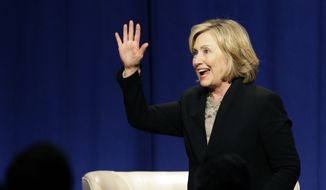 Former U.S. Secretary of State Hillary Rodham Clinton waves as she leaves the Economic Club of Chicago in Chicago on Wednesday, Oct. 8, 2014. (AP Photo/Nam Y. Huh)