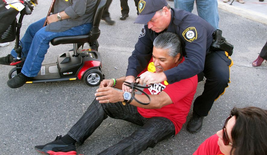Police arrest a protester sitting in a roadway in Atlantic City N.J. during a demonstration on Wednesday, Oct. 8, 2014. They were protesting givebacks demanded by the owners of the Trump Taj Mahal Casino Resort in return for keeping the casino open. The company wants to eliminate employee health care and pension plans. Twenty four of the workers were arrested in the protest. (AP Photo/Wayne Parry)