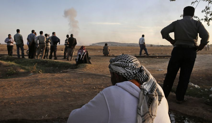 Turkish Kurds watch as airstrikes hit Kobani, inside Syria, as fighting intensifies between Syrian Kurds and the militants of Islamic State group, in Mursitpinar, on the outskirts of Suruc, at the Turkey-Syria border, Wednesday, Oct. 8, 2014. Kobani, also known as Ayn Arab and its surrounding areas have been under attack since mid-September, with militants capturing dozens of nearby Kurdish villages. (AP Photo/Lefteris Pitarakis)