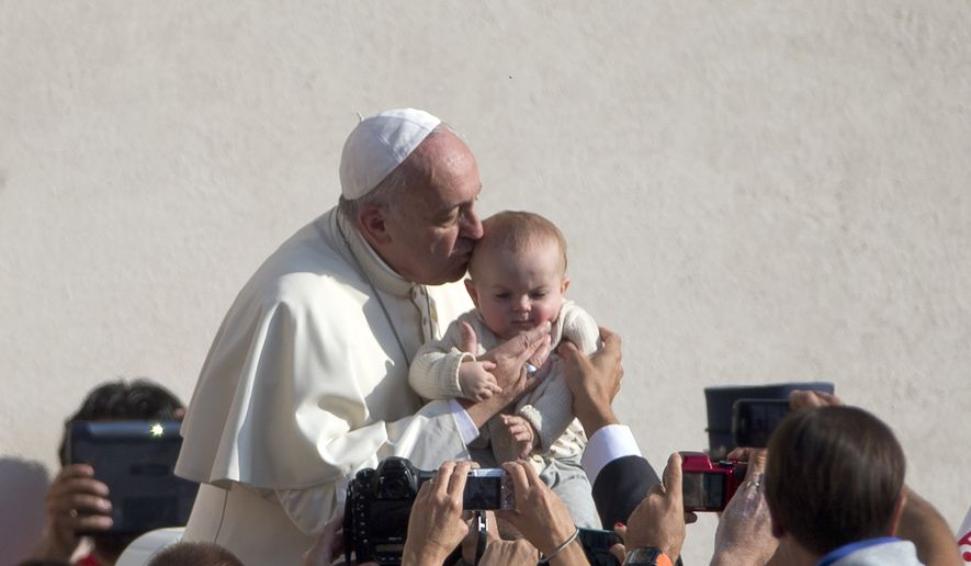 Pope Francis kisses a child as he arrives for his weekly general audience in St. Peter's Square at the Vatican, Wednesday, Oct. 8, 2014. (AP Photo/Alessandra Tarantino)
