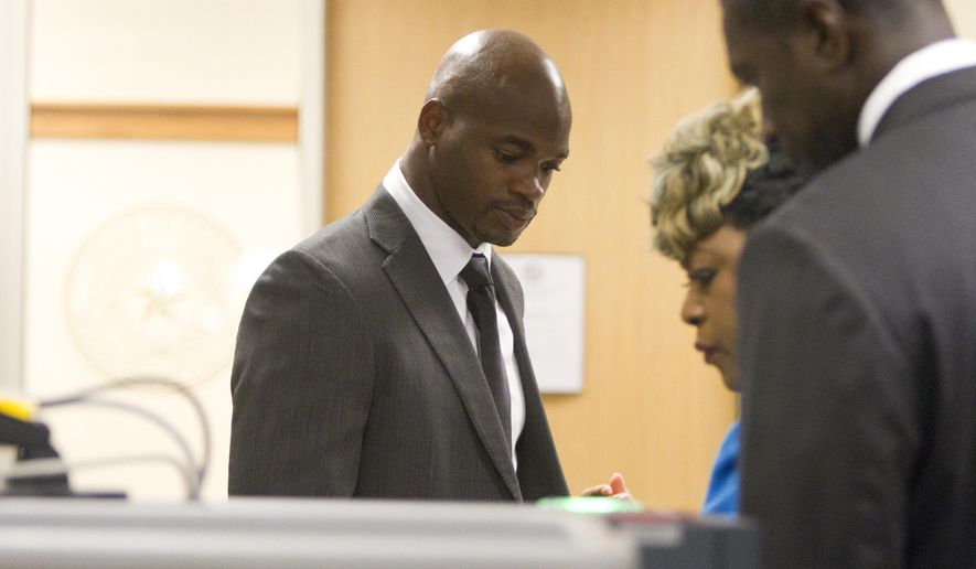Minnesota Vikings running back Adrian Peterson goes through security at the Lee G. Alworth Building as he arrives for court in Conroe, Texas Wednesday, Oct. 8, 2014. Peterson arrived to face a charge of felony child abuse for using a wooden switch to discipline his 4-year-old son earlier this year. (AP Photo/ Conroe Courier, Jason Fochtman)