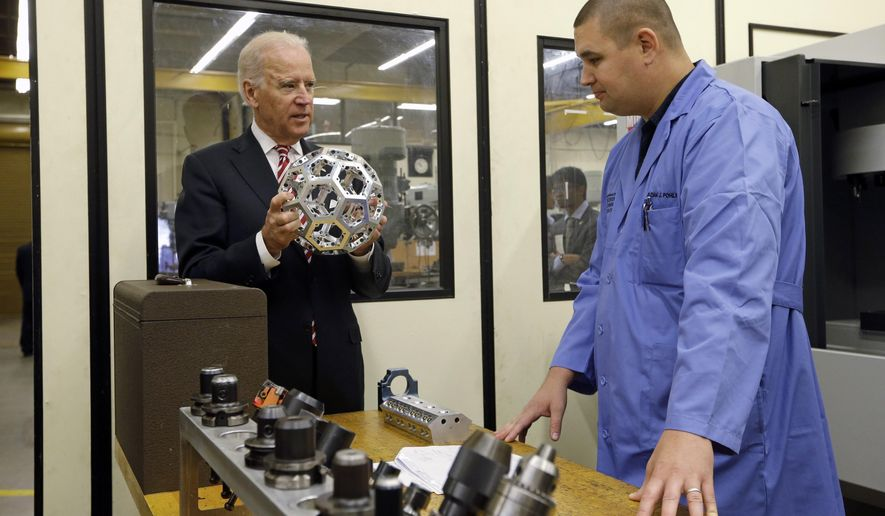Vice President Joe Biden holds a machine tooled metal ball made in the shop as he talks with instructor Adam Pohlman while visiting Renton Technical College in Renton, Wash.,Thursday, Oct. 9, 2014. Biden's appearance at Renton Technical College was part of a West Coast political swing for the vice president. Washington's two Democratic senators, Patty Murray and Maria Cantwell, joined Biden at the technical college, which received funding as part of a $450 million federal labor and training grant. (AP Photo/Elaine Thompson)