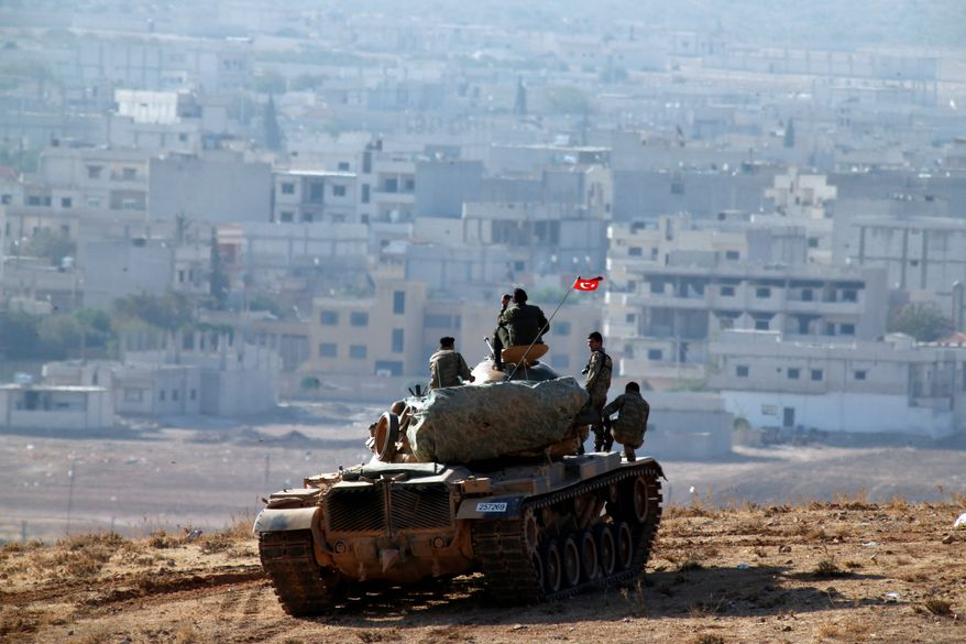 Turkish soldiers on a tank hold their position on a hilltop on the outskirts of Suruc, at the Turkey-Syria border, overlooking Kobani, Syria, during fighting between Syrian Kurds and the militants of Islamic State group, Thursday, Oct. 9, 2014.