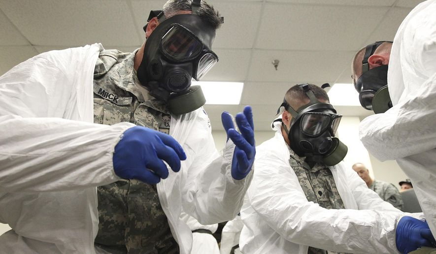 CORRECTS TRANS REFERENCE NUMBER AND OUTS - Sgt. Joel Miick, left, and Spc. Michael Potts don gas masks while training with the rest of the 36th Engineer Brigade at Fort Hood on how to put on protective clothing and gloves on Thursday, Oct. 9, 2014. The brigade is set to deploy to Liberia as part of Operation United Assistance where they will be building temporary medical facilities in helping the country fight the Ebola virus outbreak. The 450 soldiers from the brigade will be among the first to be deployed from Fort Hood to Liberia. (AP Photo/San Antonio Express-News, Kin Man Hui)