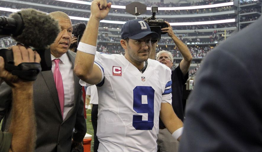 Dallas Cowboys' Tony Romo (9) celebrates their 20-17 overtime win against the Houston Texans as he walks off the field after an NFL football game, Sunday, Oct. 5, 2014, in Arlington, Texas. (AP Photo/Tim Sharp)