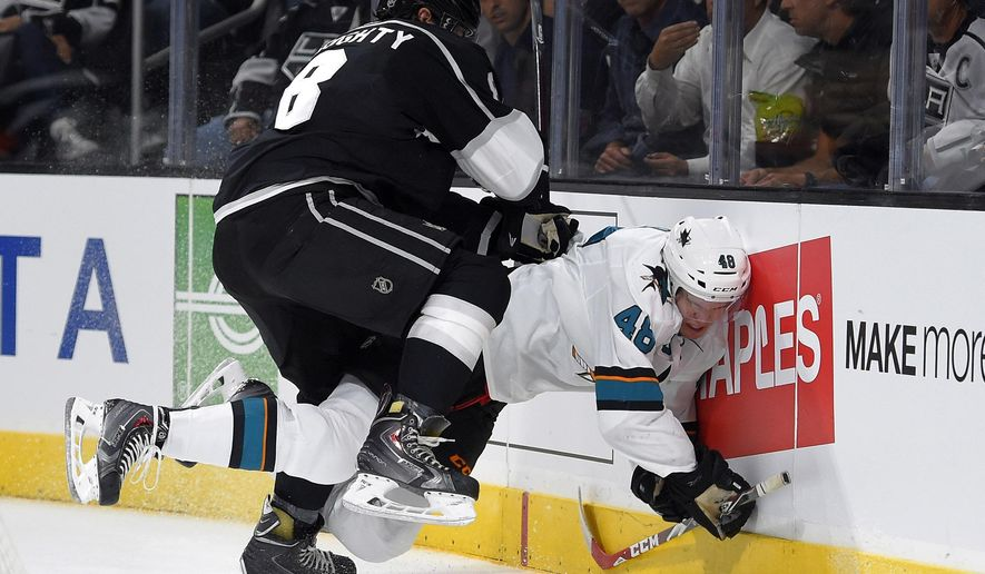 San Jose Sharks center Tomas Hertl, right, of the Czech Republic, is pushed into the boards by Los Angeles Kings defenseman Drew Doughty during the first period of an NHL hockey game, Wednesday, Oct. 8, 2014, in Los Angeles. Doughty received a penalty for boarding on the play. (AP Photo/Mark J. Terrill)