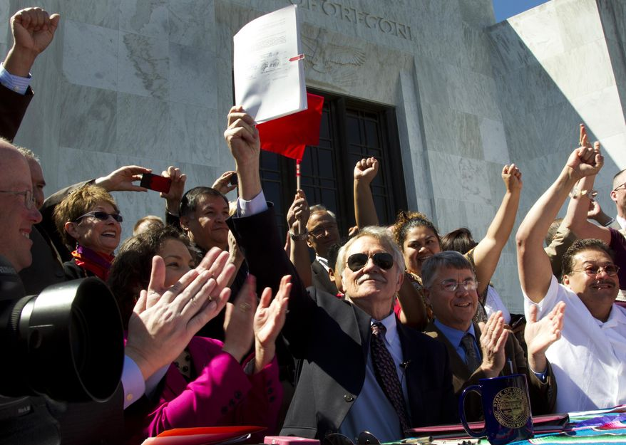 FILE - In this May 1, 2013, file photo, Oregon Gov. John Kitzhaber holds up Senate Bill 833, which authorizes driver's cards for those without the documents to obtain regular driver's licenses, after signing it into law on the steps of the State Capitol in Salem, Ore. Around the country, Oregon is among some states that have been granting more privileges to immigrants as immigration reform fails to make any headway in Congress. (AP Photo/The Oregonian, Beth Nakamura, File)