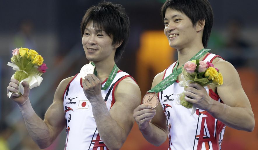 Gold medalist gymnast Kohei Uchimura of Japan, left, and his teammate Bronze medalist Yusuke Tanaka pose with their medals after the awards ceremony of the men's all-round final of the Artistic Gymnastics World Championship at the Guangxi Gymnasium in Nanning, capital of southwest China's Guangxi Zhuang Autonomous Region Thursday, Oct. 9, 2014. (AP Photo/Andy Wong)