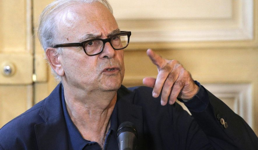 "French novelist Patrick Modiano points during a press conference at his publishing house in Paris, Thursday, Oct. 9, 2014.  Patrick Modiano, who has made a lifelong study of the Nazi occupation and its effects on his country, won the 2014 Nobel Prize in literature Thursday for what one academic called ""crystal clear and resonant"" prose. (AP Photo/Christophe Ena)"
