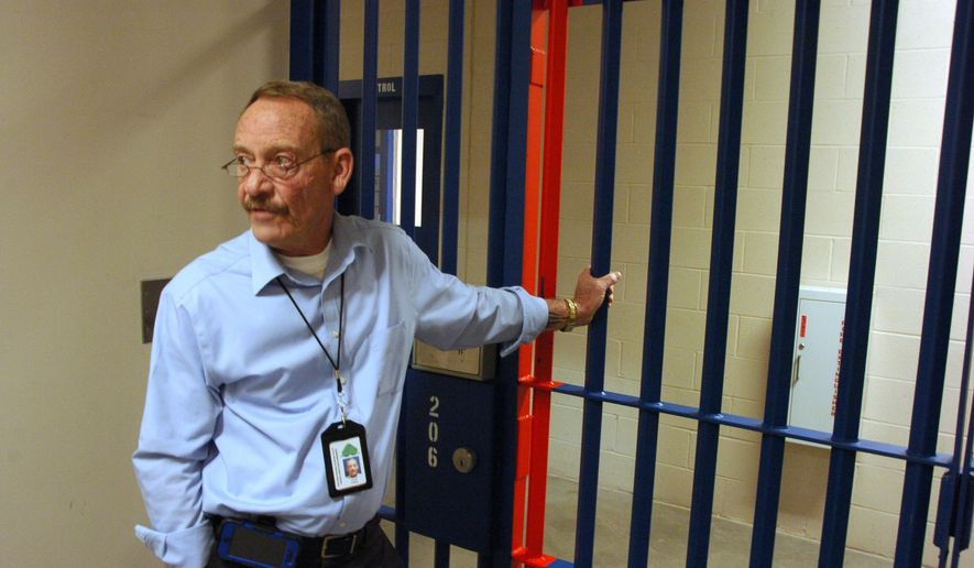 Two Rivers Regional Detention Facility Warden Ken Keller waits for a locked gate to be opened inside the 464-bed facility that has started taking in inmates after sitting empty for seven years in Hardin, Mont., on Wednesday, Oct. 8, 2014. The jail is now run by Emerald Correctional Management, which is getting inmates from across the Northern Plains under a contract with the U.S. Bureau of Indian Affairs. (AP Photo/Matthew Brown)