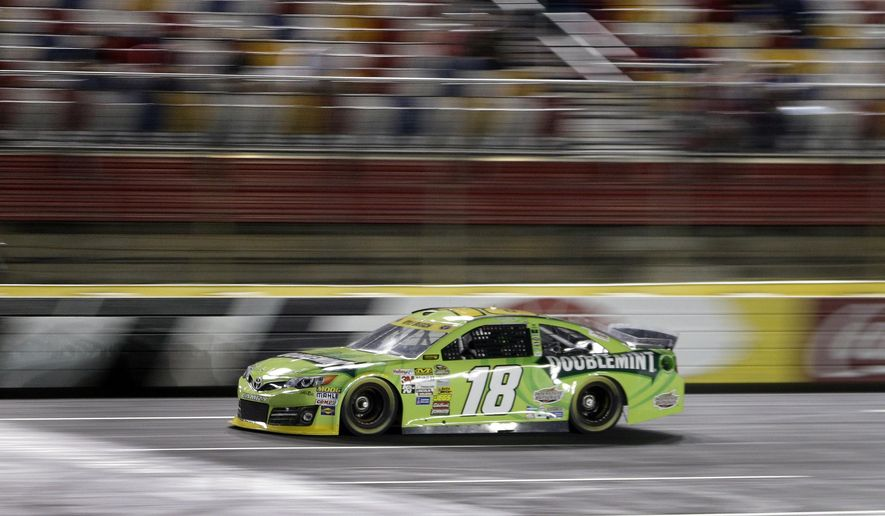 Kyle Busch drives his car qualifying for Saturday's NASCAR Bank of America Sprint Cup series auto race at Charlotte Motor Speedway in Concord, N.C., Thursday, Oct. 9, 2014. Busch won the pole position for the race with a lap of 197.390 mph. (AP Photo/Chuck Burton)