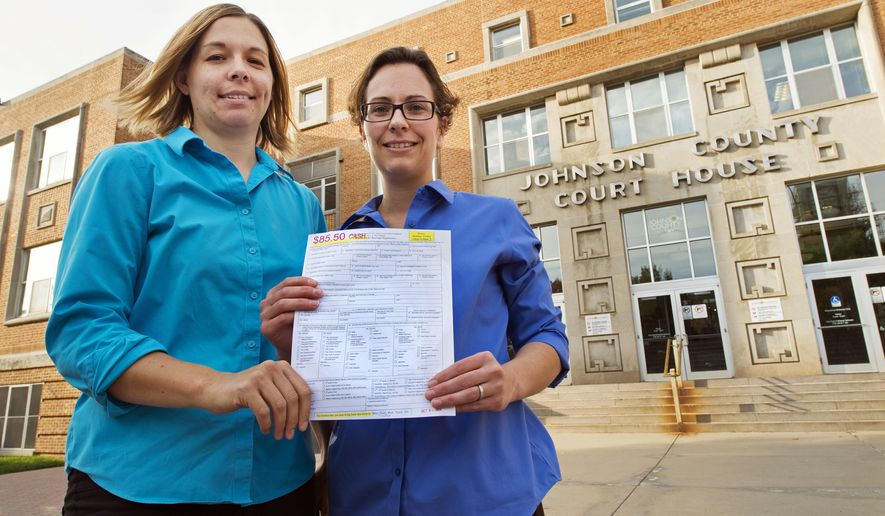 Angela Schaefer, left, and partner, Jennifer Schaefer hold an application for a marriage license at the clerk's office at the Johnson County Courthouse in Olathe, Kan., Wednesday, Oct. 8, 2014. They are due to obtain their license Tuesday, after the weekend and the Columbus Day holiday Monday. (AP Photo/The Kansas City Star, Tammy Ljungblad)