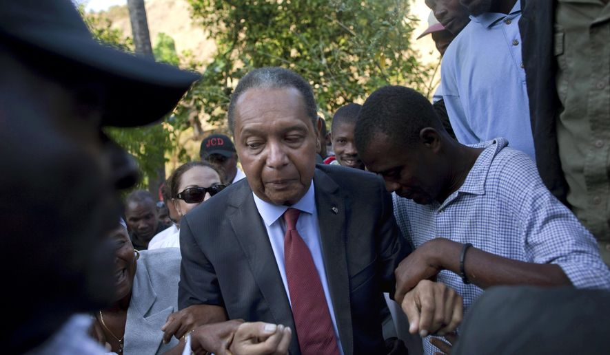 "FILE - In this Feb. 8, 2011 file photo, former Haitian dictator Jean-Claude ""Baby Doc"" Duvalier's supporters help him negotiate an uneven path during a visit to his mother's hometown and grave site in Leogane, Haiti. Duvalier, the self-designated ""president-for-life"" who died Oct. 4, 2014, from an apparent heart attack, will not get a formal state funeral, but have a ""simple, private,""funeral arranged by friends and family in Haiti, attorney Reynolds Georges said in an interview. (AP Photo/Ramon Espinosa, File)"