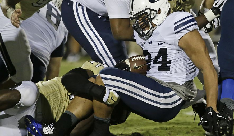 Brigham Young running back Algernon Brown, right, is tackled after a short gain by Central Florida linebacker Terrance Plummer, left, during the first half of an NCAA college football game in Orlando, Fla., Thursday, Oct. 9, 2014. (AP Photo/John Raoux)