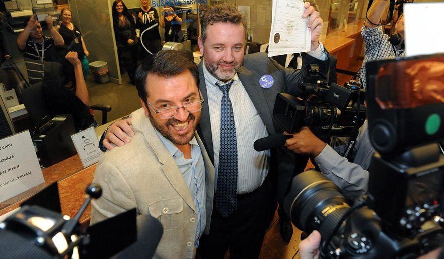 In this photo provided by the Las Vegas News Bureau, Antioco Carri and Theo Small hold-up their marriage license after being the first couple in line at the Clark County Marriage License Bureau in Downtown on Thursday, Oct. 9, 2014. (AP Photo/Las Vegas News Bureau, Brian Jones)
