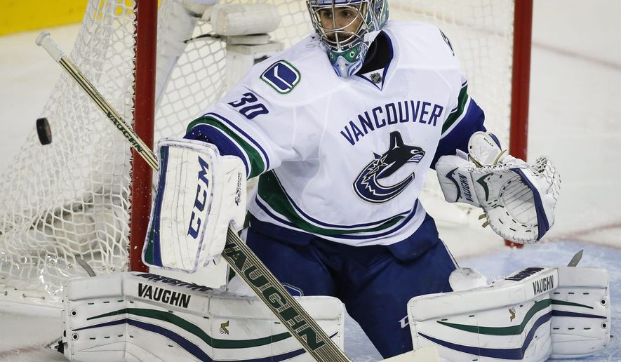Vancouver Canucks goalie Ryan Miller swats away the puck during third period NHL hockey action against the Calgary Flames in Calgary, Alberta, Wednesday, Oct. 8, 2014.  (AP Photo/The Canadian Press, Jeff McIntosh)