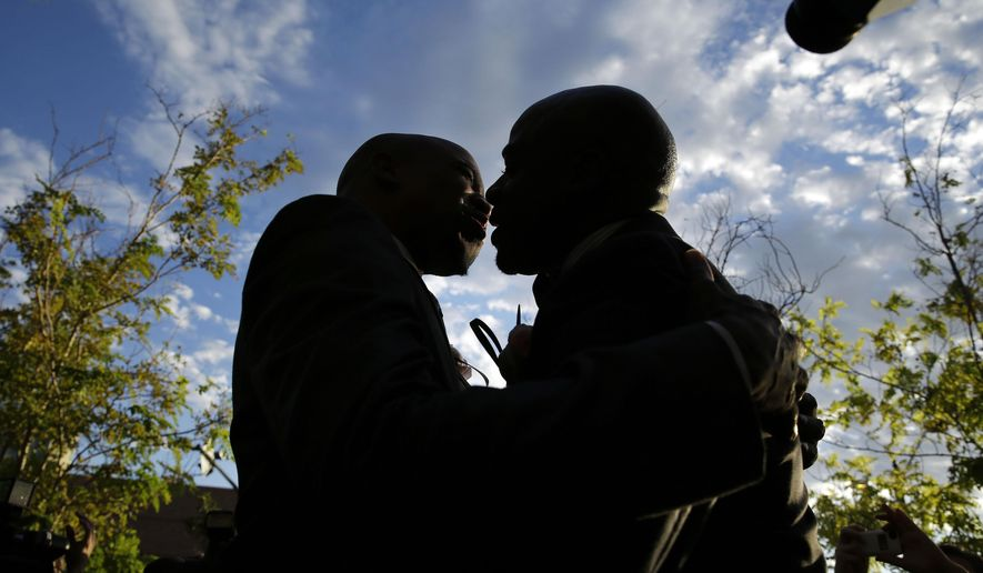 Sherwood Howard, left, embraces Nevada State Sen. Kelvin Atkinson as they get married outside of the Marriage License Bureau, Thursday, Oct. 9, 2014, in Las Vegas. The two had just obtained a same-sex marriage license and were the first same-sex couple married in Las Vegas. (AP Photo/John Locher)