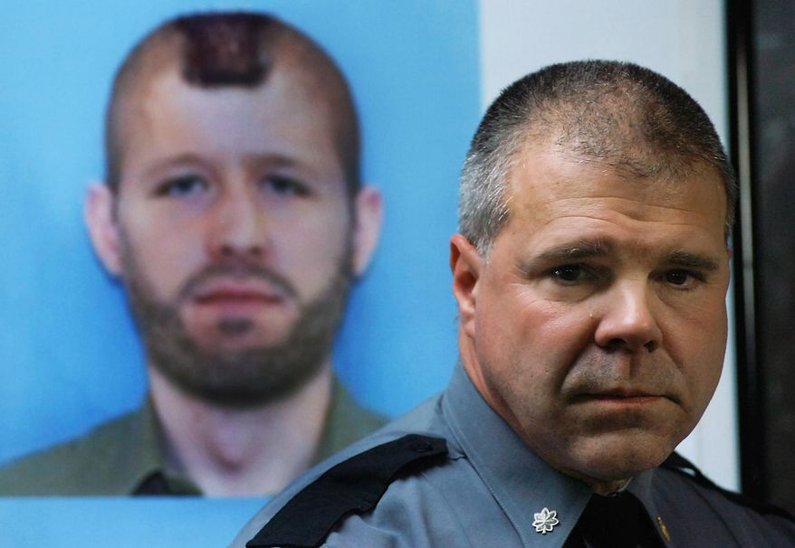 Pennsylvania State Police Lt. Col. George Bivens addresses the media during a news conference on Wednesday, Oct. 8, 2014, at the Blooming Grove Township Municipal Building in Blooming Grove, Pa.  In background is an enhanced photo of suspected killer Eric Frein who has been hiding in the deep woods in the Pocono's for over three weeks. (AP Photo/Scranton Times & Tribune, Butch Comegys)  WILKES BARRE TIMES-LEADER OUT; MANDATORY CREDIT