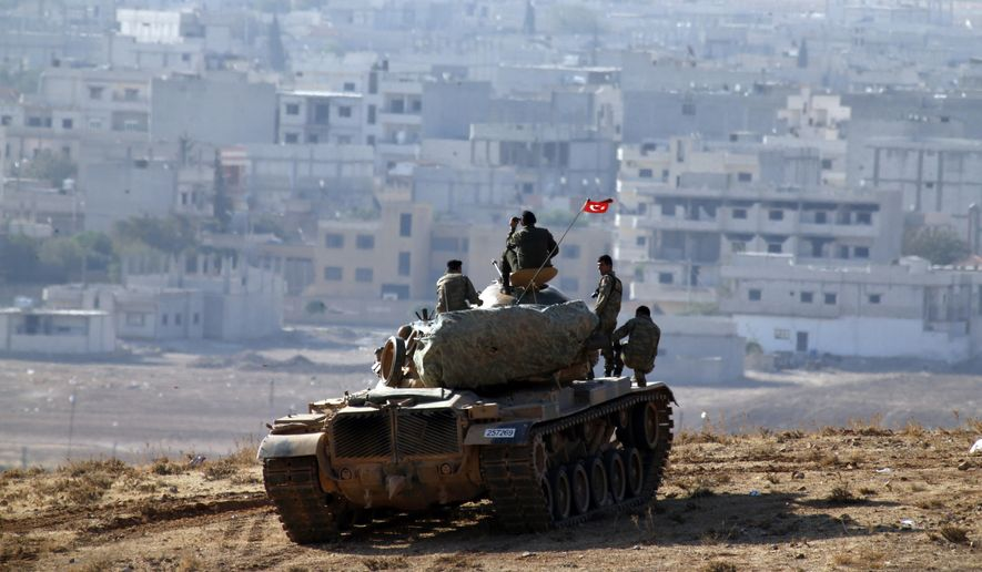 Turkish soldiers on a tank hold their position on a hilltop on the outskirts of Suruc, at the Turkey-Syria border, overlooking Kobani, Syria, during fighting between Syrian Kurds and the militants of Islamic State group, Thursday, Oct. 9, 2014. The fighting over Kobani has brought Syria's civil war yet again to Turkey's doorstep and allies have tried to press Ankara to take a more robust role in the U.S.-led coalition to fight the Islamic State group. (AP Photo/Lefteris Pitarakis)