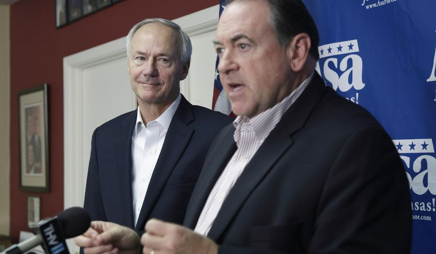 Republican candidate for Arkansas governor Asa Hutchinson, left, listens as former Arkansas Gov. Mike Huckabee speaks during a news conference at Republican Party of Arkansas headquarters in Little Rock, Ark., Thursday, Oct. 9, 2014. Huckabee is campaigning for Republicans on his home turf, finding that a political landscape that had been dominated by Democrats since Reconstruction is now a two-party state. (AP Photo/Danny Johnston)