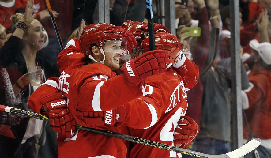 Detroit Red Wings center Gustav Nyquist, of Sweden, celebrates his goal against the Boston Bruins with teammates in the second period of a NHL hockey game in Detroit Thursday, Oct. 9, 2014. (AP Photo/Paul Sancya)