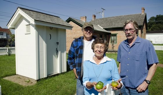 ADVANCE FOR USE SUNDAY, OCT. 12 AND THEREAFTER - In this Sept. 17, 2014 photo, Richard Dombroski, MaryLouise Agnew and Terry Buckaloo stand with the tomatoes that were harvested from the 150-year-old heirloom tomato seeds found in the privy of the Lincoln-Manahan Home in Sterling, Ill. (AP Photo/Sauk Valley Media, Philip Marruffo)
