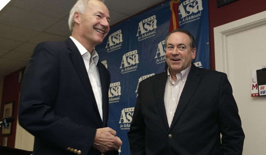 Republican candidate for Arkansas governor Asa Hutchinson, left, talks with former Arkansas Gov. Mike Huckabee at Republican Party of Arkansas headquarters in Little Rock, Ark., Thursday, Oct. 9, 2014. Huckabee is campaigning for Republicans on his home turf, finding that a political landscape that had been dominated by Democrats since Reconstruction is now a two-party state. (AP Photo/Danny Johnston)