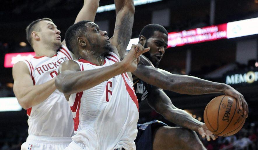 Memphis Grizzlies' Earl Clark, right, passes the ball around Houston Rockets Donatas Motiejunas, left, and Kostas Papanikolaou in the second half of an NBA exhibition basketball game Thursday, Oct. 9, 2014, in Houston. (AP Photo/Pat Sullivan)