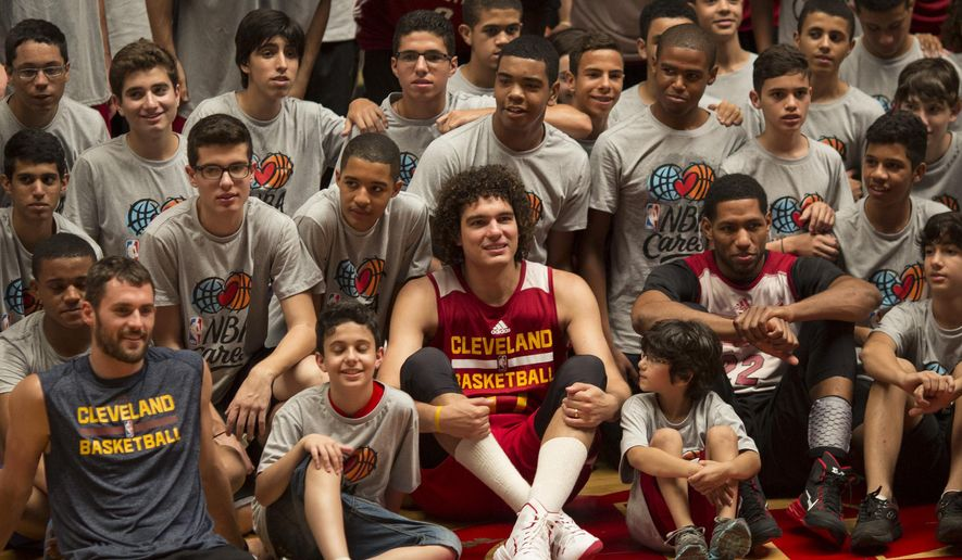 The Cleveland Cavaliers' Anderson Varejao, center, poses for photos with kids before the start of a training session in Rio de Janeiro, Brazil, Thursday, Oct. 9, 2014. The Cleveland Cavaliers will play the Miami Heat in a preseason game in Rio, on Saturday, as part of the NBA Global Games. (AP Photo/Felipe Dana)