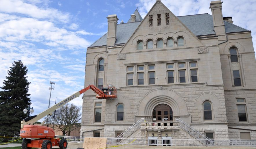 Workers with Masonry Construction repair damage to the stone walls of the Gage County Courthouse, Beatrice, Neb., Tuesday, Oct. 7, 2014. The project was supposed to start last month, but rain pushed the repairs, estimated at $11,300, into October. (AP Photo/Beatrice Daily Sun, Scott Koperski)