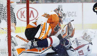 Washington Capitals' Liam O'Brien (87) collides with Philadelphia Flyers' Ray Emery (29) during the first period of a preseason NHL hockey game, Monday, Sept. 22, 2014, in Philadelphia. (AP Photo/Matt Slocum)