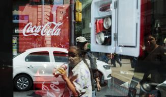 A woman is reflected in a Coca-Cola store window display as she drinks a Coke in Mexico City, Thursday, Oct. 9, 2014. Recent declines suffered by Coke and Pepsi in Mexico underscore why the beverage industry is fighting tax proposals on sugary drinks in San Francisco and Berkeley, Calif. (AP Photo/Rebecca Blackwell)